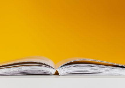 Eye level photo of an open book with a bright yellow background.