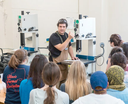 staff member instructs group of students on use of bandsaw