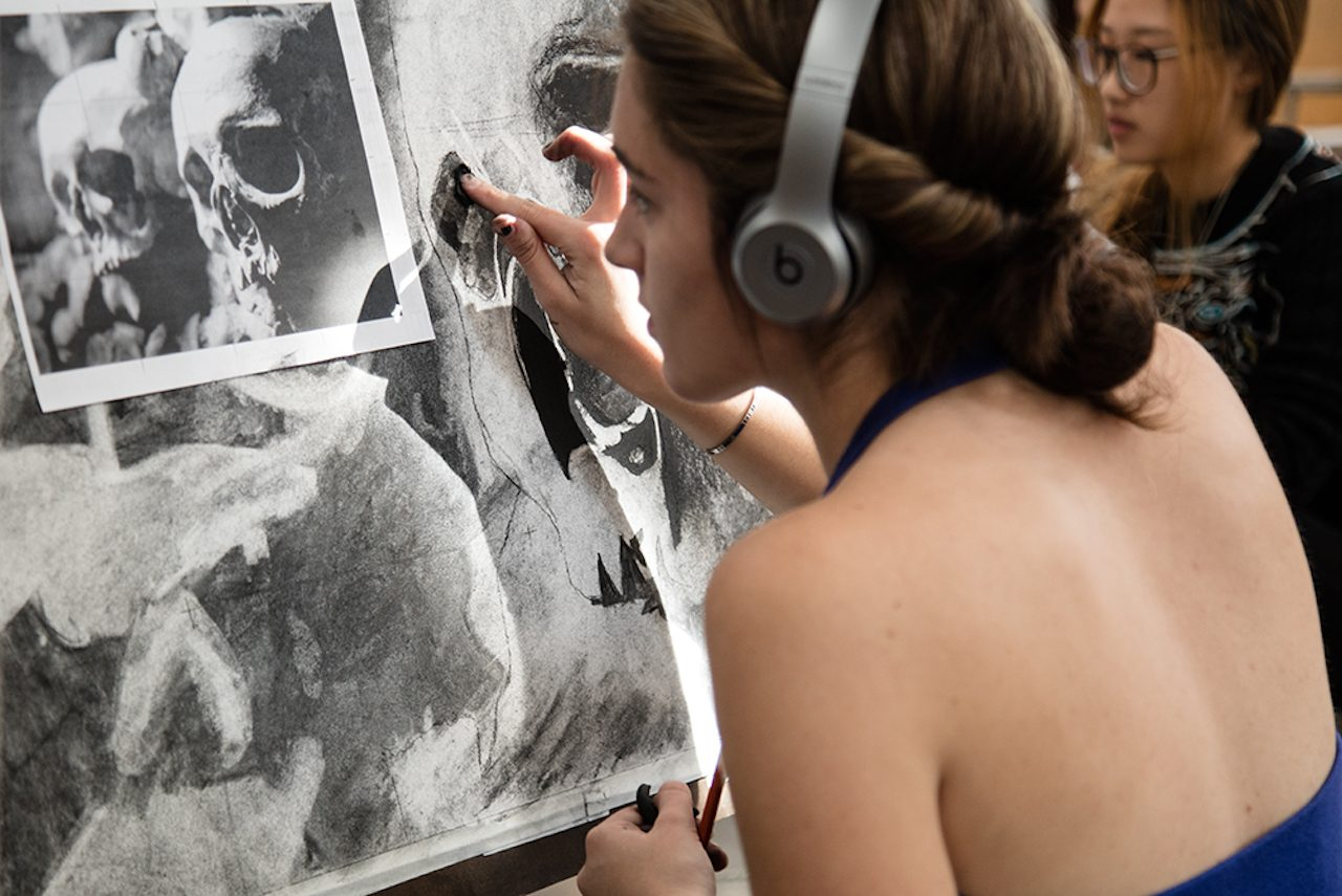 Photo of a student working on a charcoal drawing at an easel