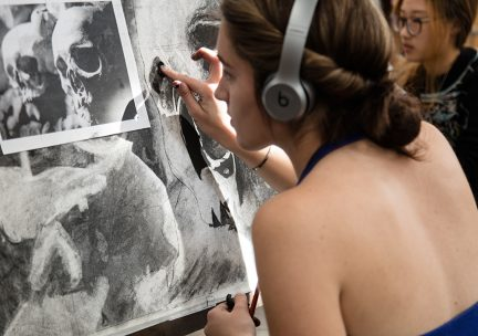 Photo of a student working on a charcoal drawing
