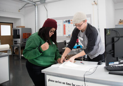 lab assistant helps student with weeding cut vinyl