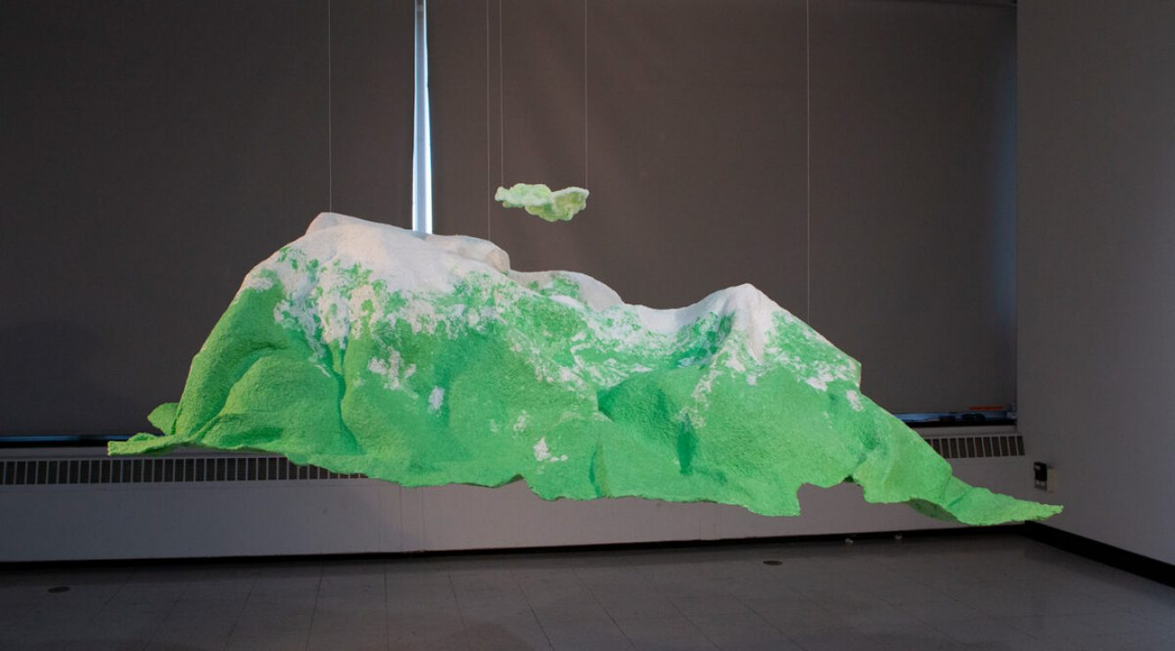 Photo of an abstract landscape sculpture that looks like green landforms with white peaks suspended in a darkened gallery
