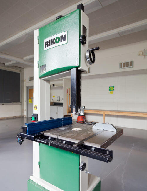 a green bandsaw in a woodshop