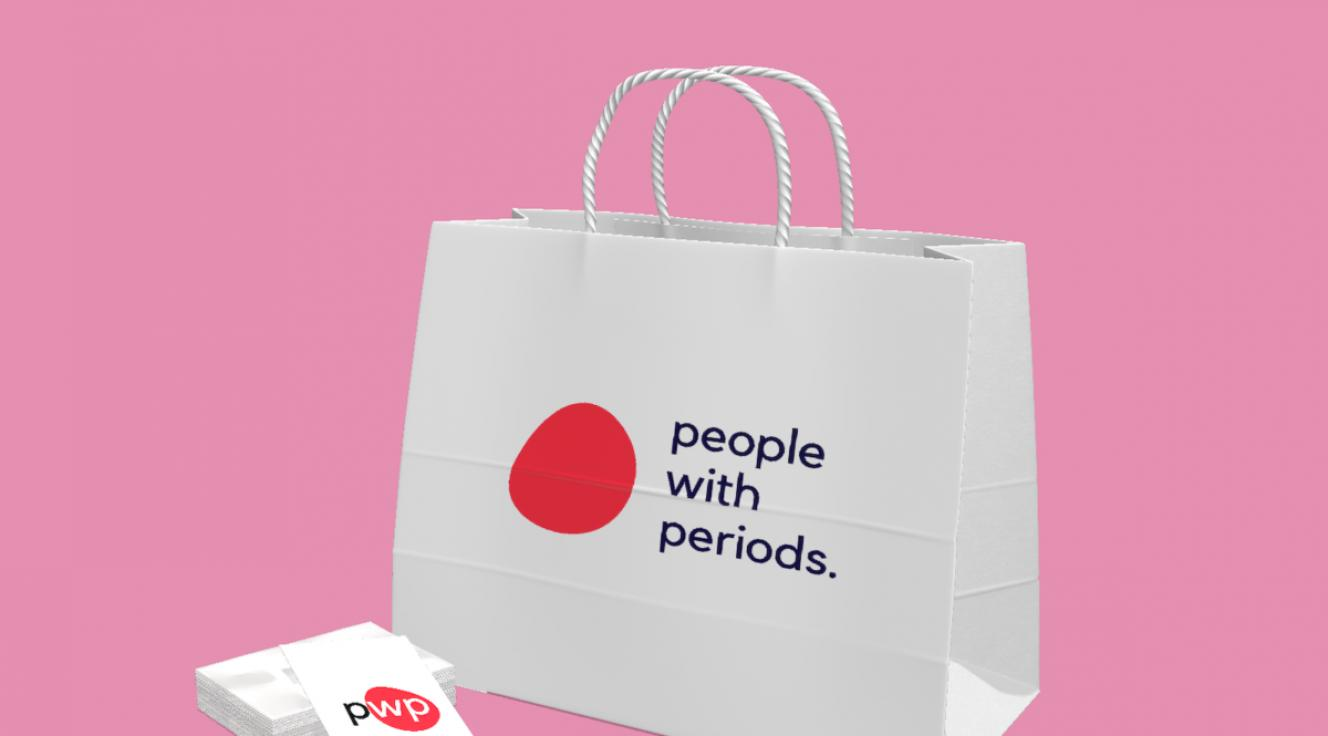 Digital image of a paper shopping bag and brochure with a red spot and the words