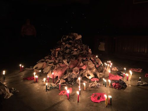 Photo of a pile of undergarments in a dark space lit by candles