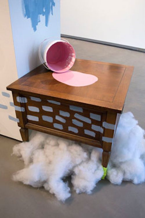 Photo of art installation with pink paint spilling on a small wooden table
