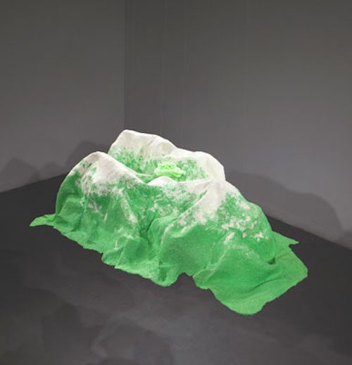 Photo of abstract sculptural artwork that looks like green mountainous landforms with white peaks