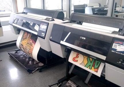 two large format inkjet printers printing artwork