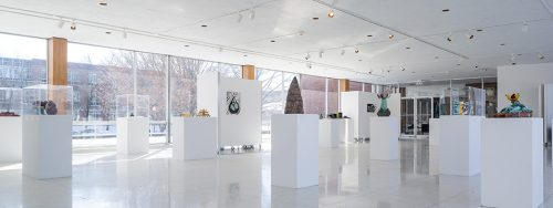 Photo of artworks on pedestals in a gallery with picture windows