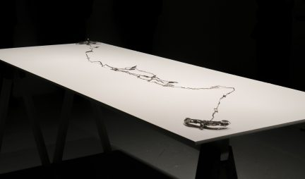 Photo of linear metal artwork arrayed across a white tabletop