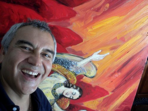 Portrait of Carlos Llerena Aguirre laughinig with a bright painting behind