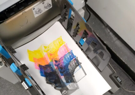 a print of a cat on a printer separated into yellow, magenta, cyan, and black