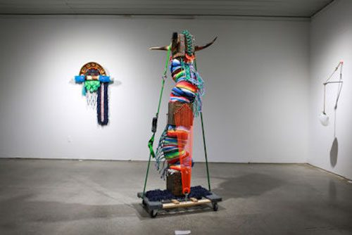 Photo of gallery installation with two colorful multimedia sculptures