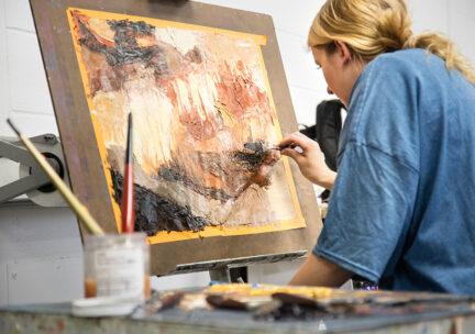 photo of a female student painting and abstract image on canvas taped to a board