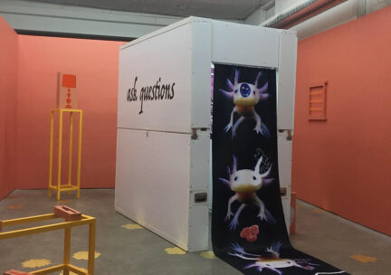 Installation of a portable, phone booth-sized art gallery, inside of a bigger art gallery with salmon colored walls.
