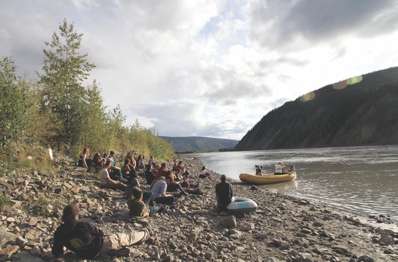 Photo of a group of students sitting on a shore, while an artist delivers a lecture from a raft in the water