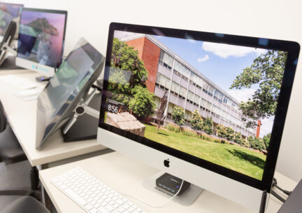 Photo of a row of imacs with the A&D building on the desktop