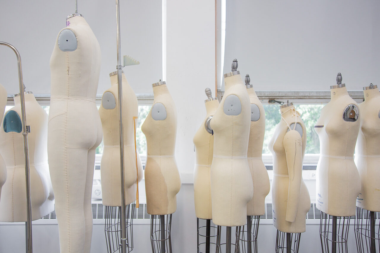 photo of yellow dress forms in front of windows