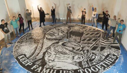 students around large medallion painted on floor