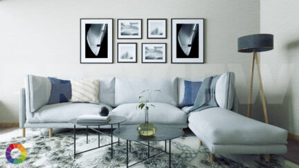 Digital image of a living room with a light blue sectional couch, two cofree tables, and a group of framed black and white photographs on the wall