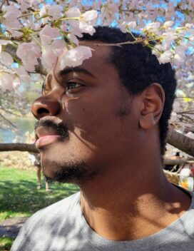 Portrait of the alumnus in profile beneath a flowering spring tree