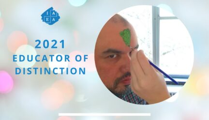 Jorge educator of distinction with someone painting green on his forehead