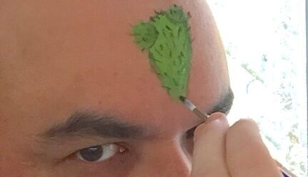 portrait of Jorge Lucero's forhead being painted a green triangle