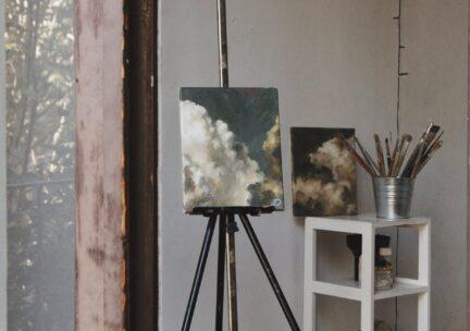 View of studio with painting of clouds on an easel