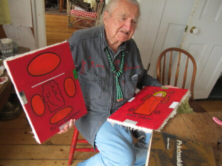Peter Bodnar sitting on chair holding two of his paintings in bold red