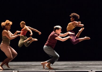 Two dancers arch their backs in a jump behind two dancers gesturing with their hands in front of their body