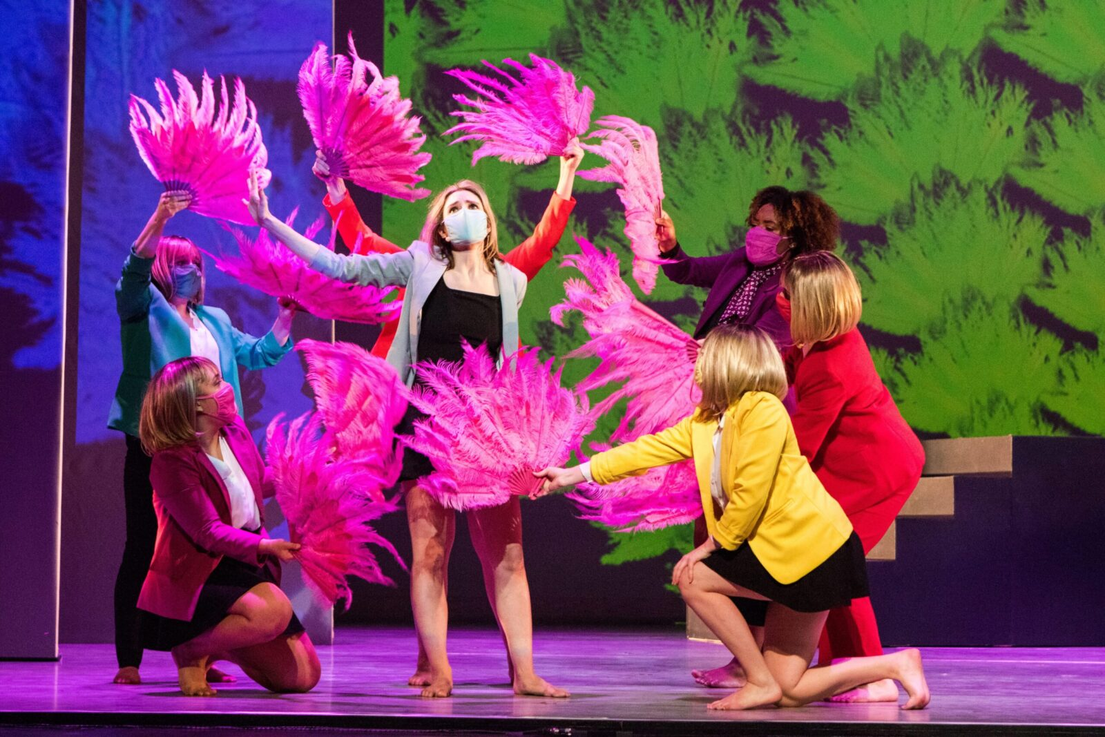 A group of dancers holding pink feathered fans surround a soloist
