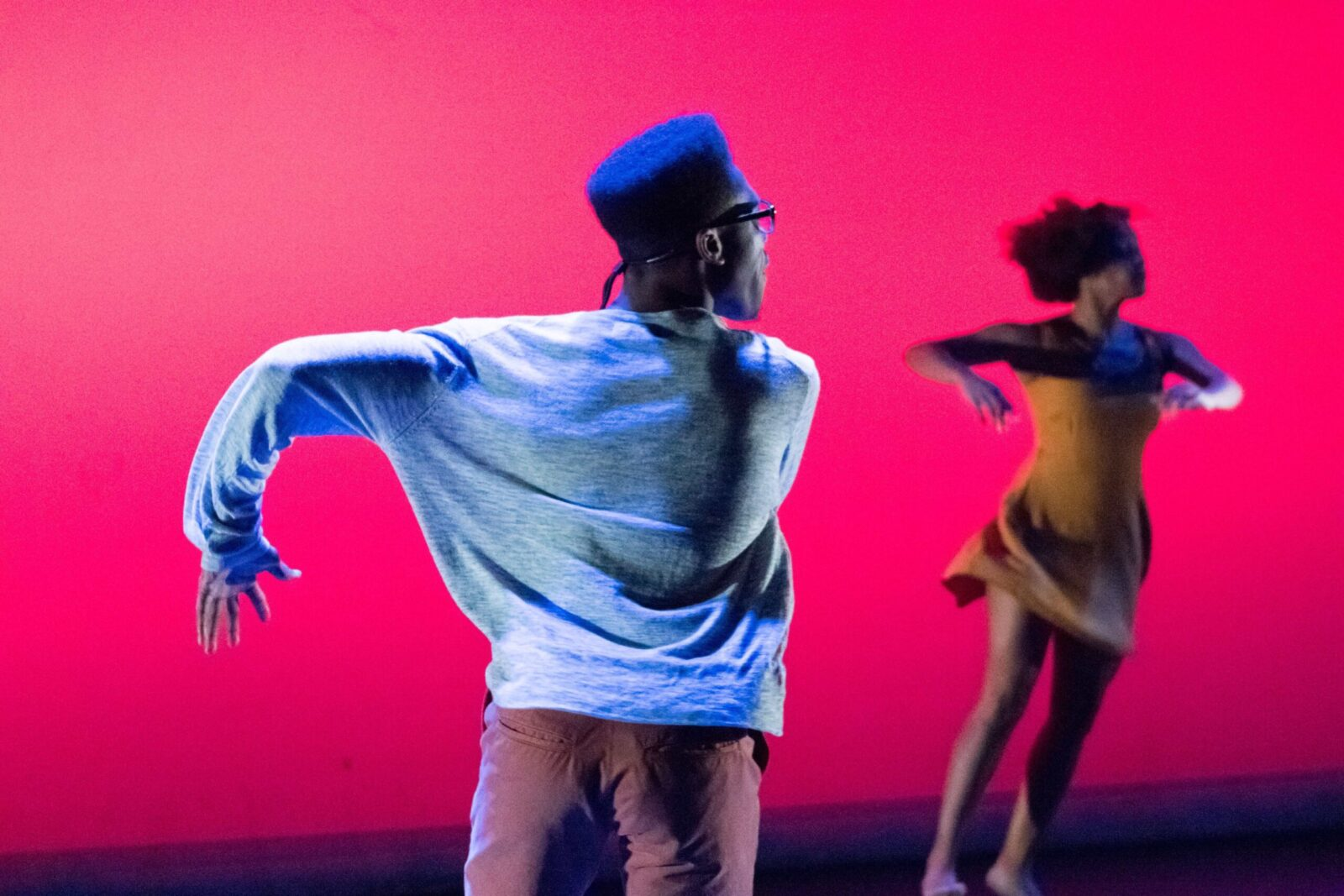 A back of a dancer with left arm outstretched in front of a red screen
