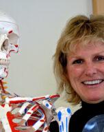 Kim smiles standing next to a anatomical skeleton