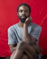 Dare sits with his legs crossed in front of a red draped background