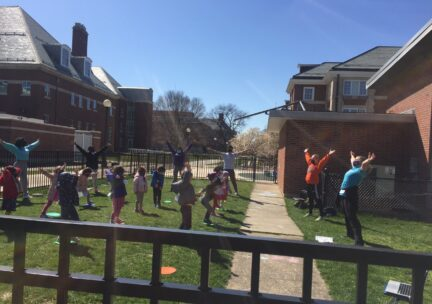 Children extend their arms out as they dance outdoors