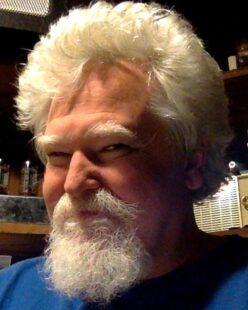 A headshot of Ken, smiling