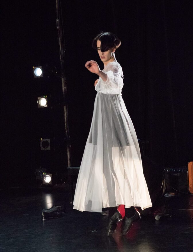 A lone dancer in a white dress and tap shoes on, reaches their left arm forward