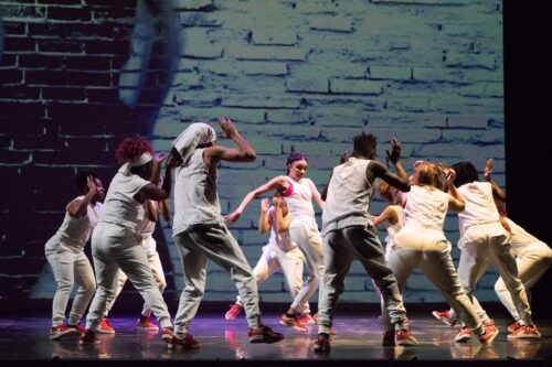 A group of dancers surround a soloist