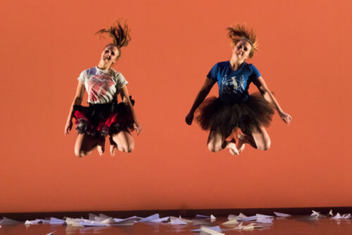 Two woman jump high up into the air