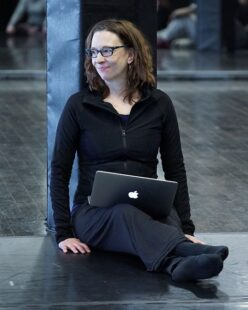 Sara sits on the floor with her laptop computer open