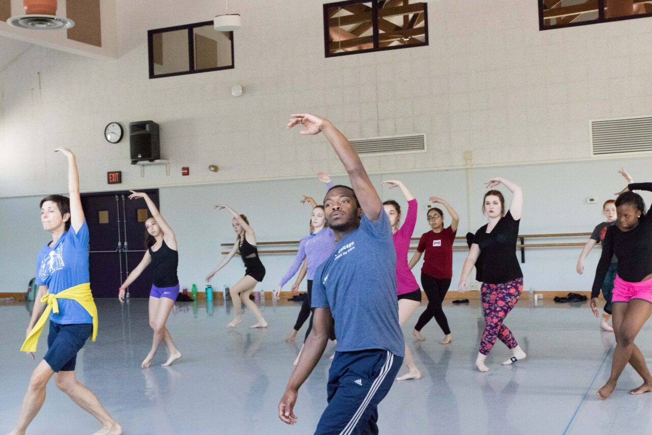A group of young dancers reach their left arm up above their heads