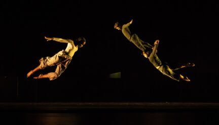 Three dancers flying through the air on stage