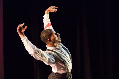 A dancers holds his arms above his head