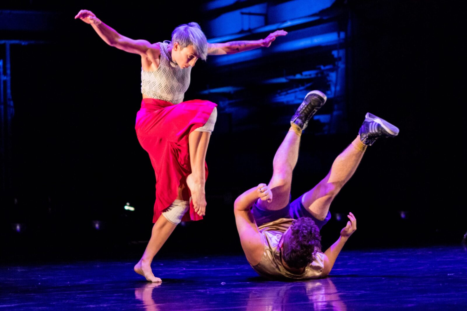 A dancer hovers over another dancer who is rolling on the ground