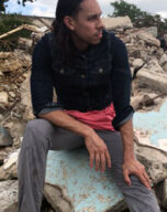 Ricardo sits on some rubble and looks over his left shoulder