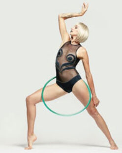 Jakki holds her right arm above her head and has a green hula hoop around her torso