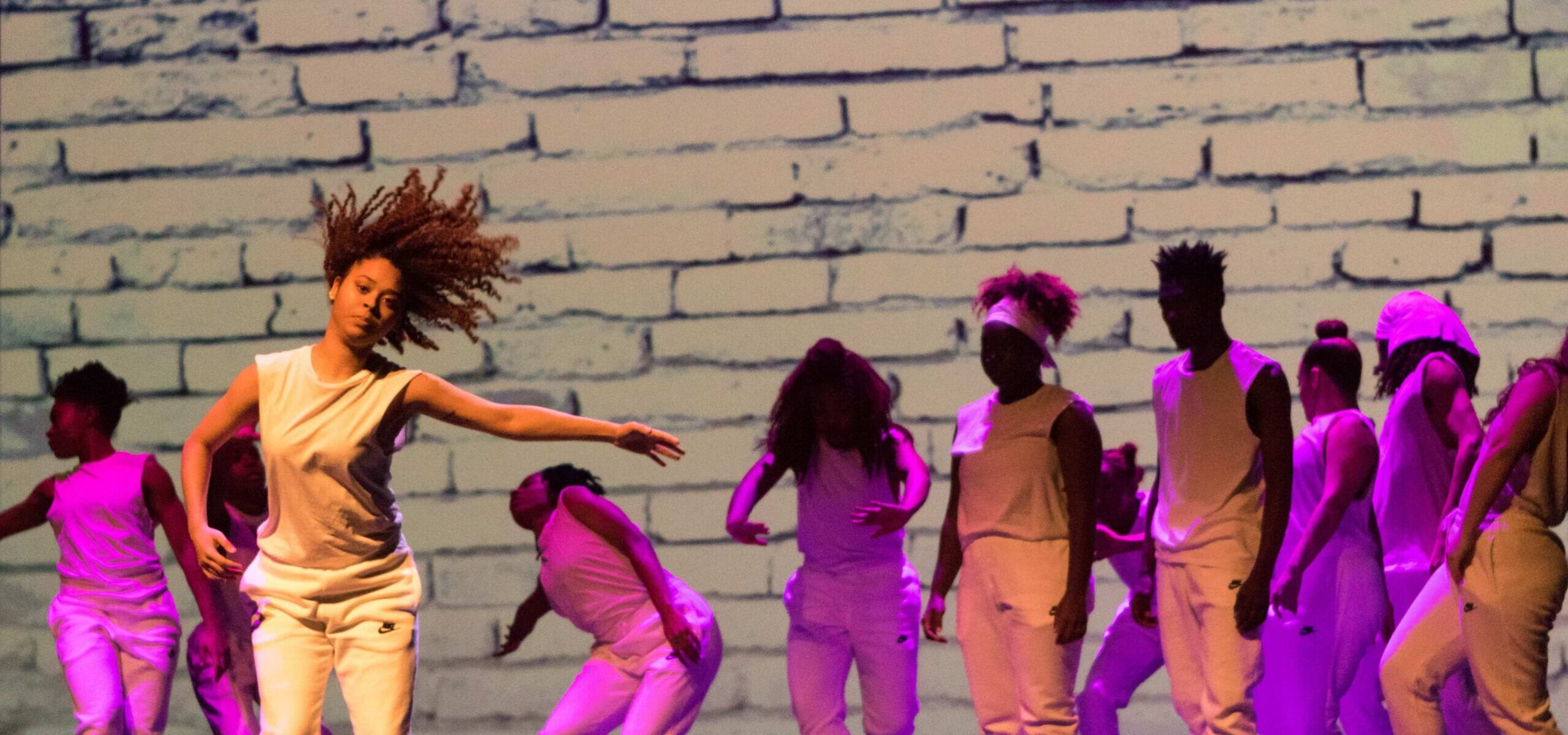 A dancer with left arm outstretched and hair flying dances in front of a group