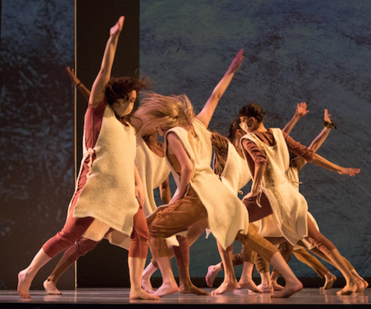 Dancers run thru each other with arms outstretched