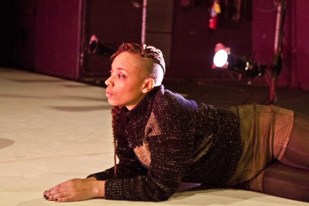 dancer laying down and looking forward with hands together