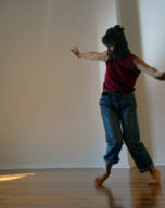 Sarah stands with inwardly rotated legs and arms outstretched